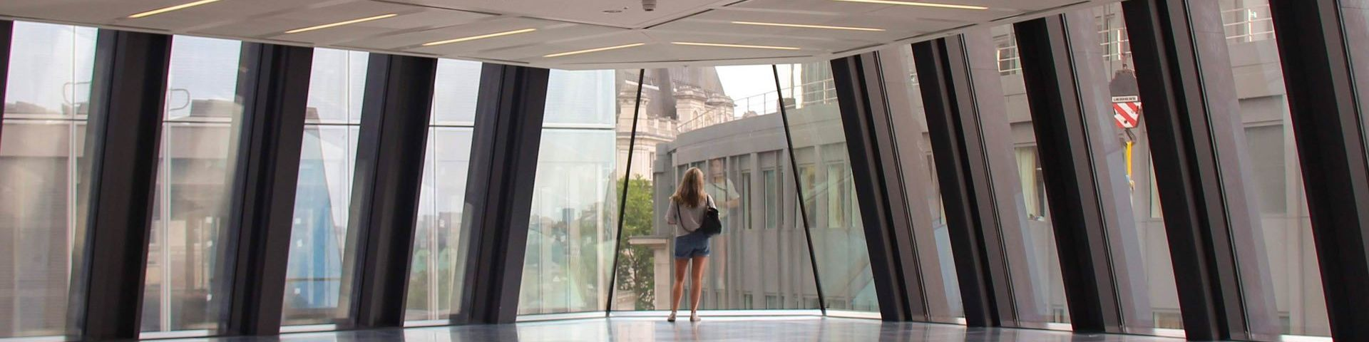 A woman with her back to the camera, standing on the floor of a glass office building
